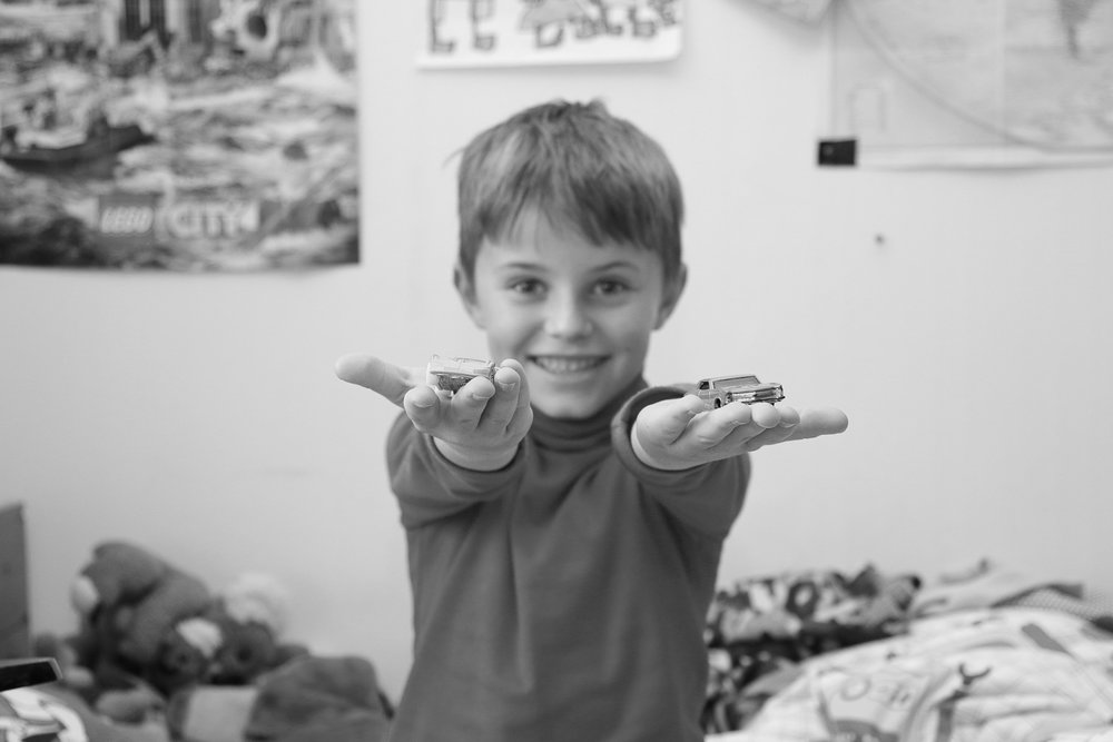 boy-showing-off-his-favourite-toy-cars-black-and-white.jpg