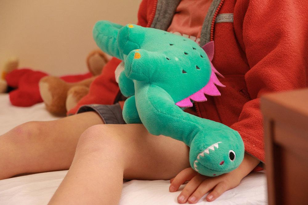 little-boy-wearing-red-holding-dinosaur-toy.jpg