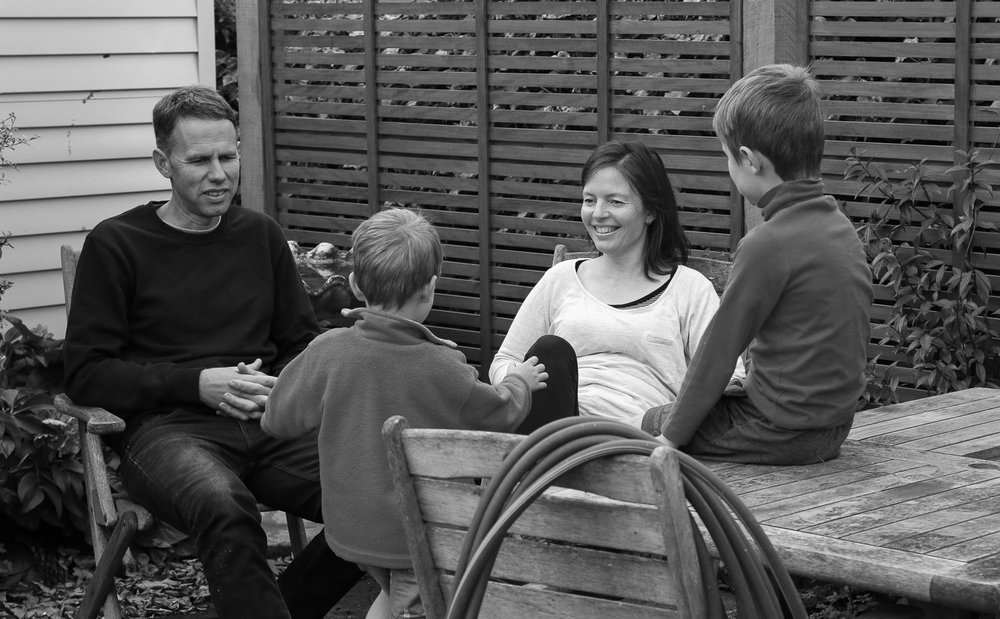 mother-and-father-and-two-boys-sitting-together-laughing-spring-afternoon-happy-together-black-and-white.jpg