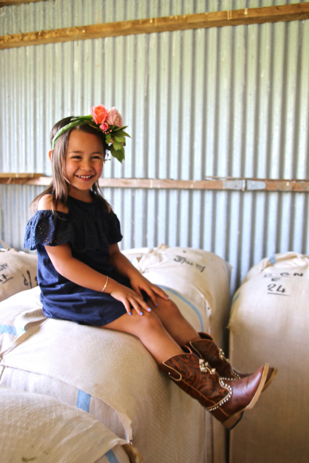 little-girl-wearing-cowboy-boots-sitting-on-wool-bale-wearing-flower-crown_L-R.jpg