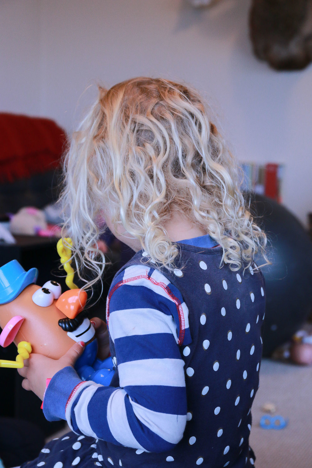 little-girl-playing-in-lounge-with-mr-potato-head-curly-blonde-hair