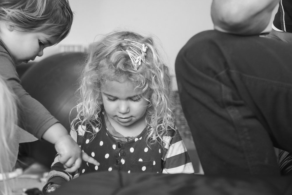 little-girl-playing-with-father-and-little-sister-wearing-clips in hair.jpg