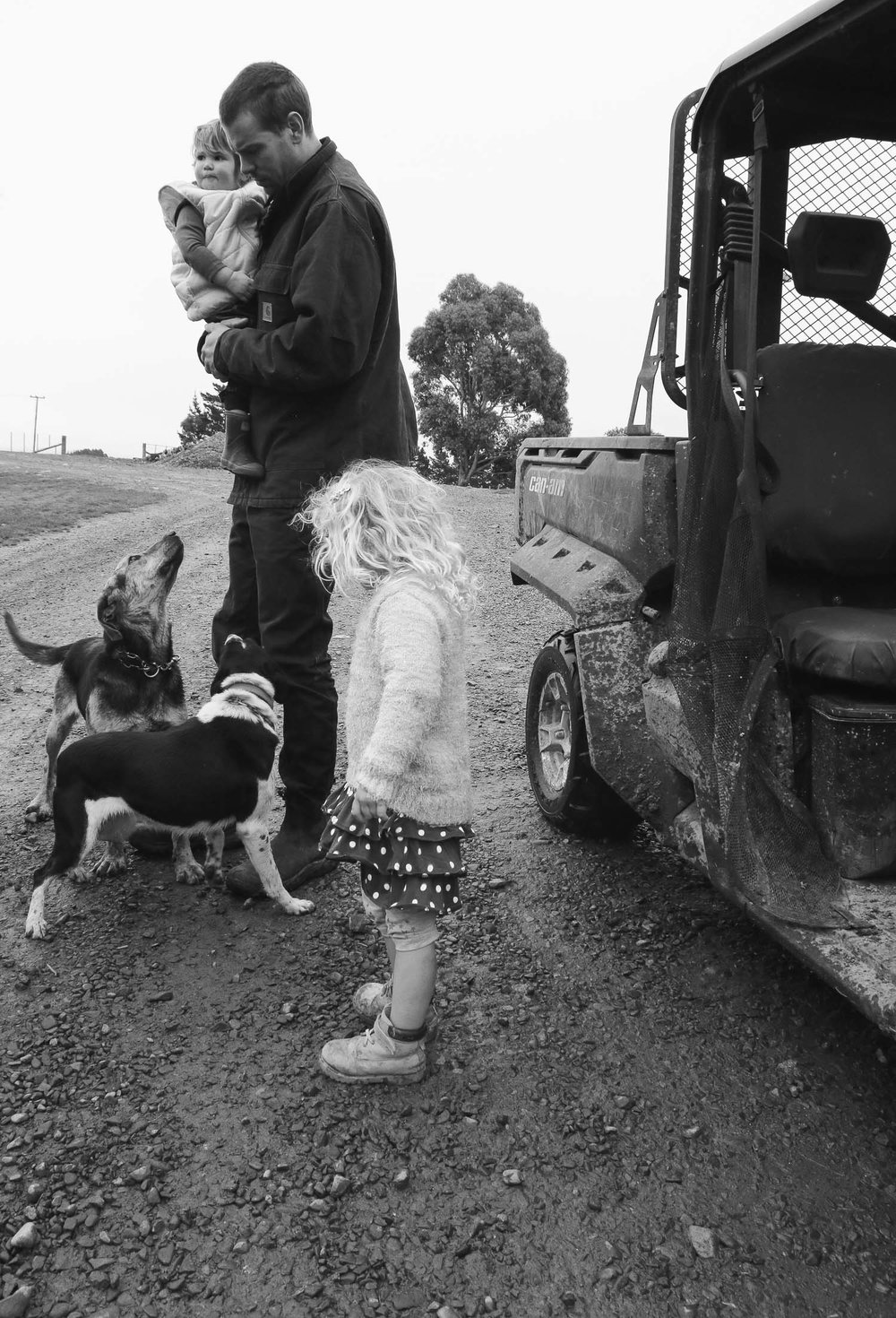 rowland-smith-shearer-standing-by-motorbike-holding-daughter-with-other-daughter-at-his-feet-dogs-around