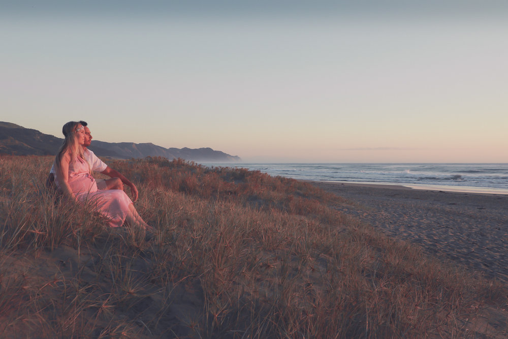 pregnant woman at beach at sunrise with husband looking out to ocean