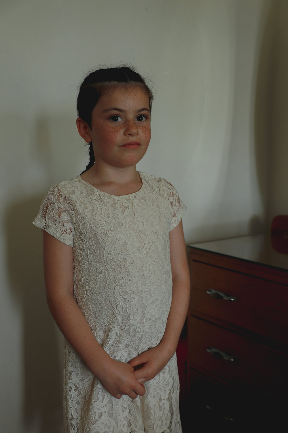 wedding-photography-flower-girl-trying-on-dress.jpg