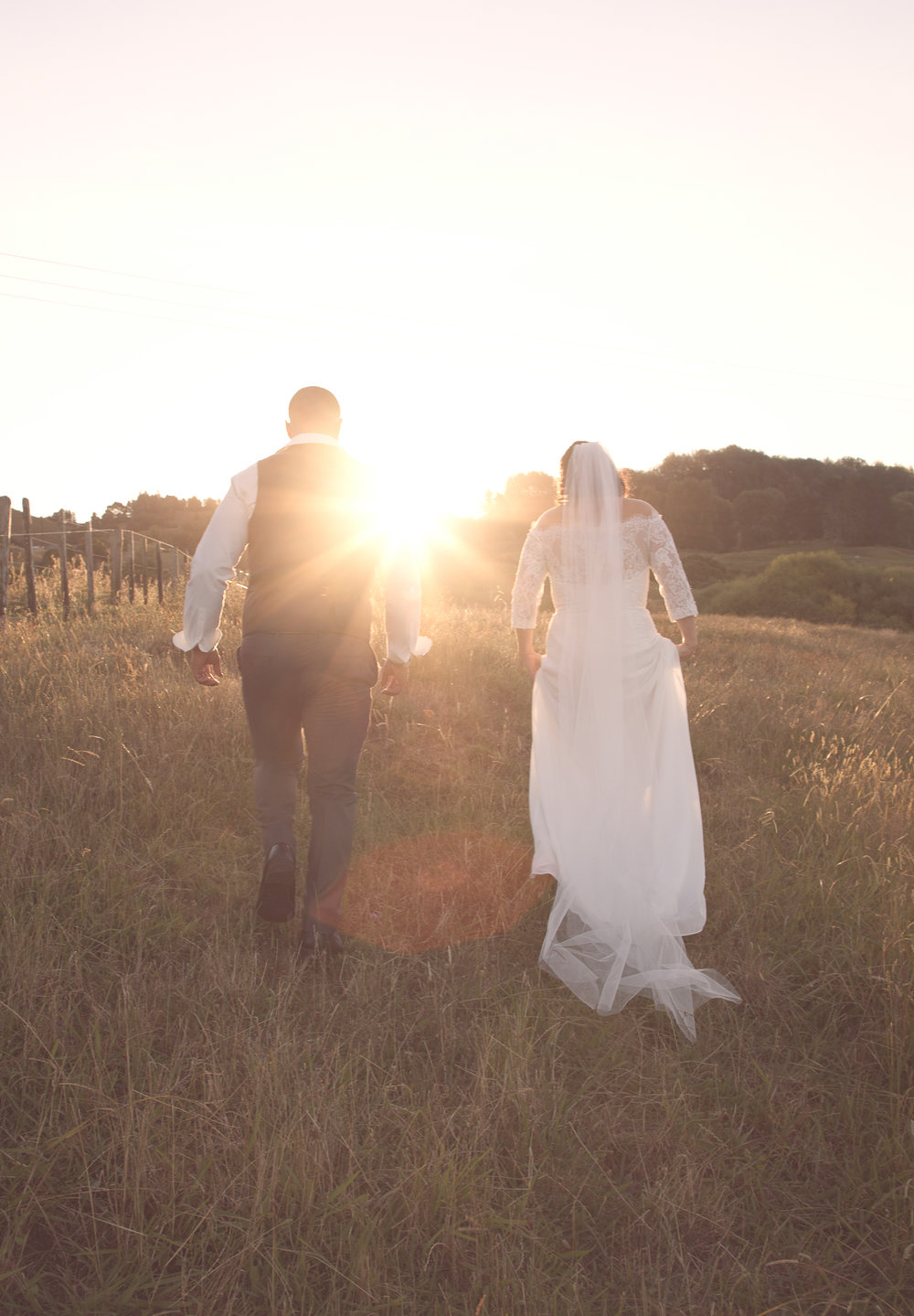 bride and groom walking into sunset on wedding day