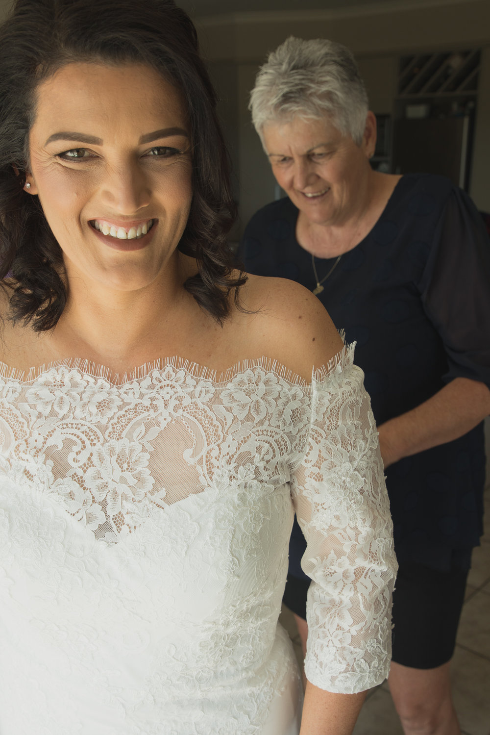 bride smiling and mother of the bride buttons up wedding dress
