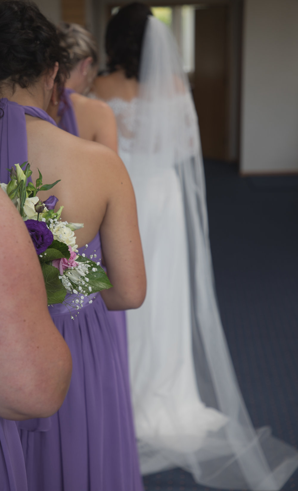 purple bridesmaid dresses and flowers at alter during ceremony