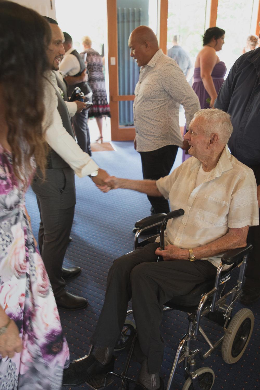 granddad in wheelchair congratulating groom