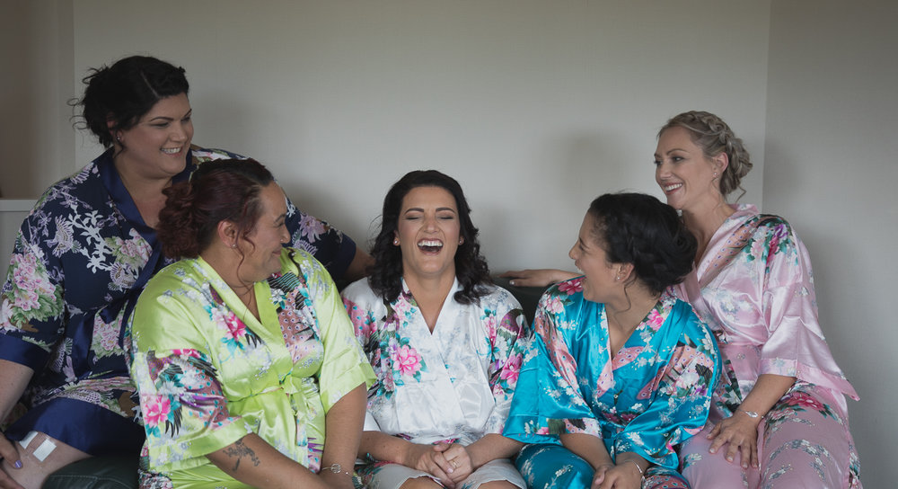 bride and bridesmaids laughing together