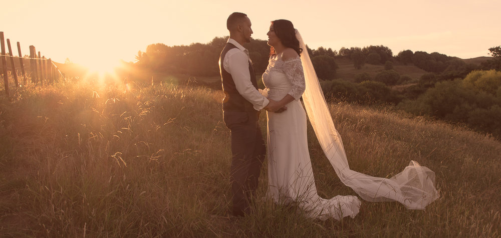 bride and groom standing together at sunset