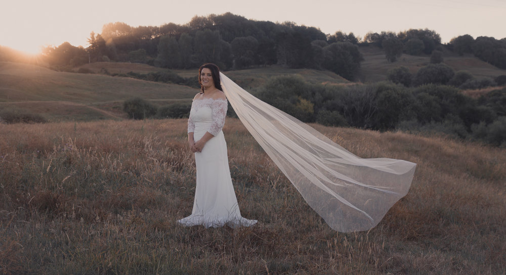 bride with veil floating at sunset on farm