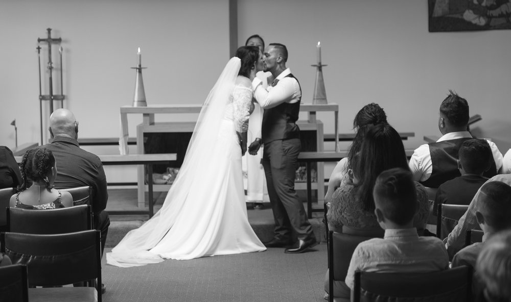 bride and groom kiss during wedding ceremony