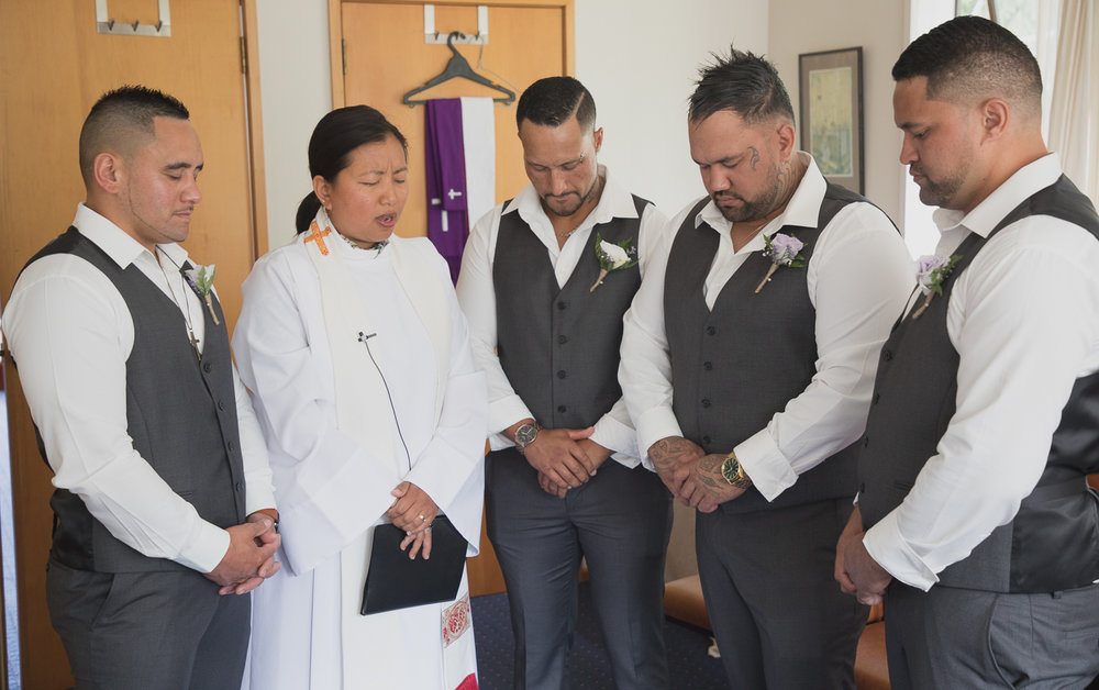 groom and groomsmen praying with the minister before ceremony
