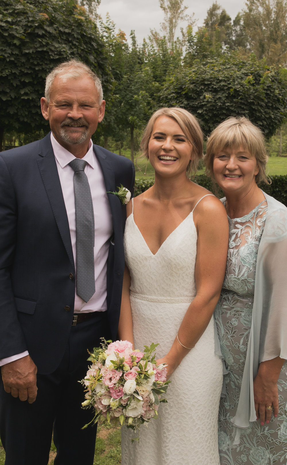 bride and her parents on her wedding day