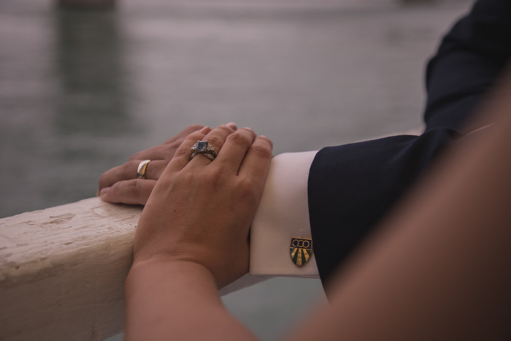 bride and groom together under Auckland Harbour Bridge with rings showing