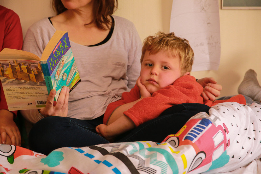 little boy listening to mum read harry potter book