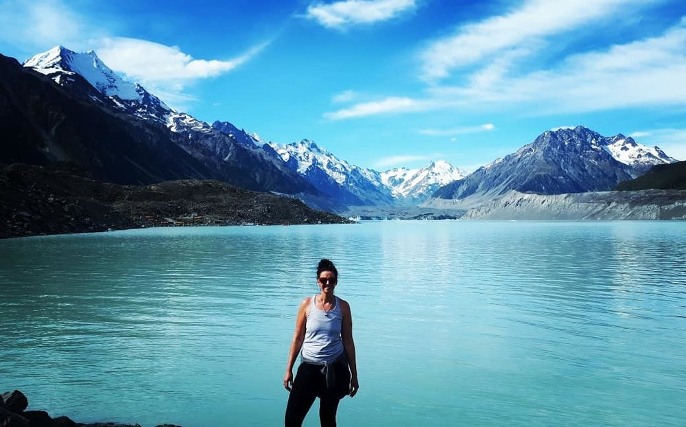 girl-standing-in-front-of-lake-with-snow-capped-mountains