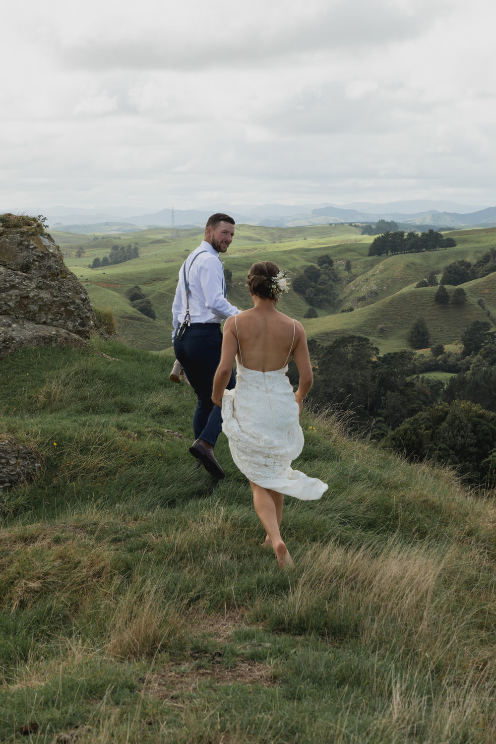 wedding-at-the-red-barn-new-zealand-wedding-photographer-groom-leading-bride-on-hilltop.jpg