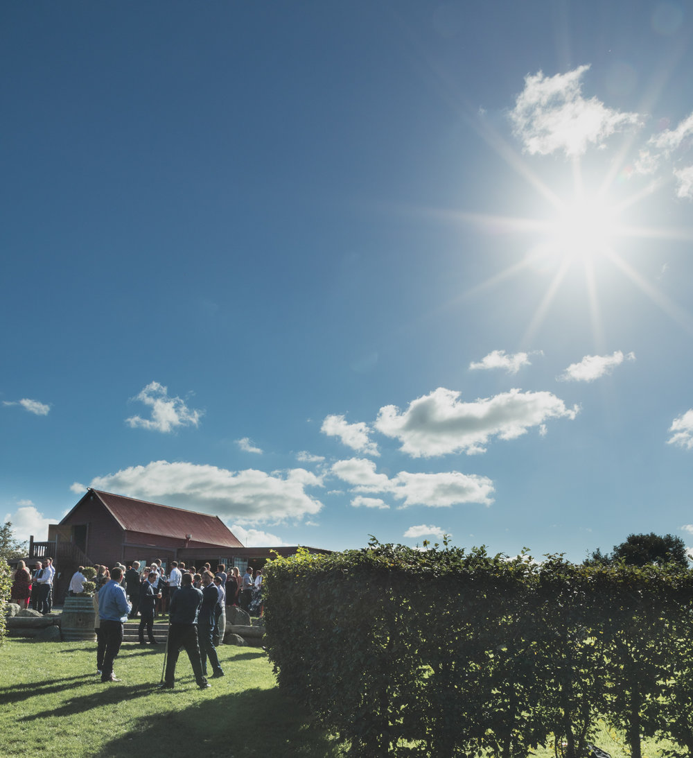 wedding-at-the-red-barn-new-zealand-wedding-photographer-sun-over-red-buildings.jpg