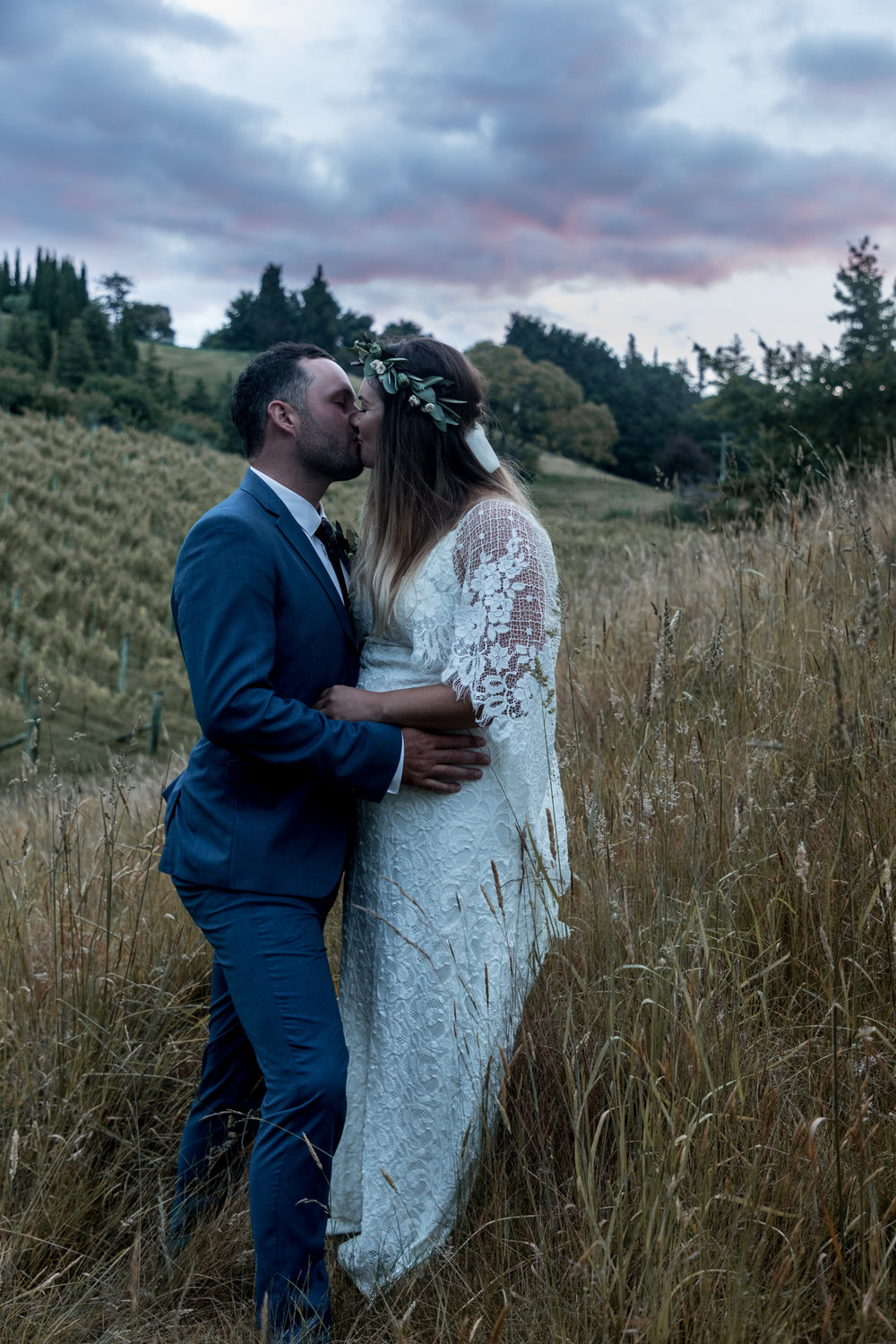 black-barn-winery-wedding-hawkes-bay-wedding-photographer-bride-and-groom-at-sunset-cuddling-in-purple-light.jpg