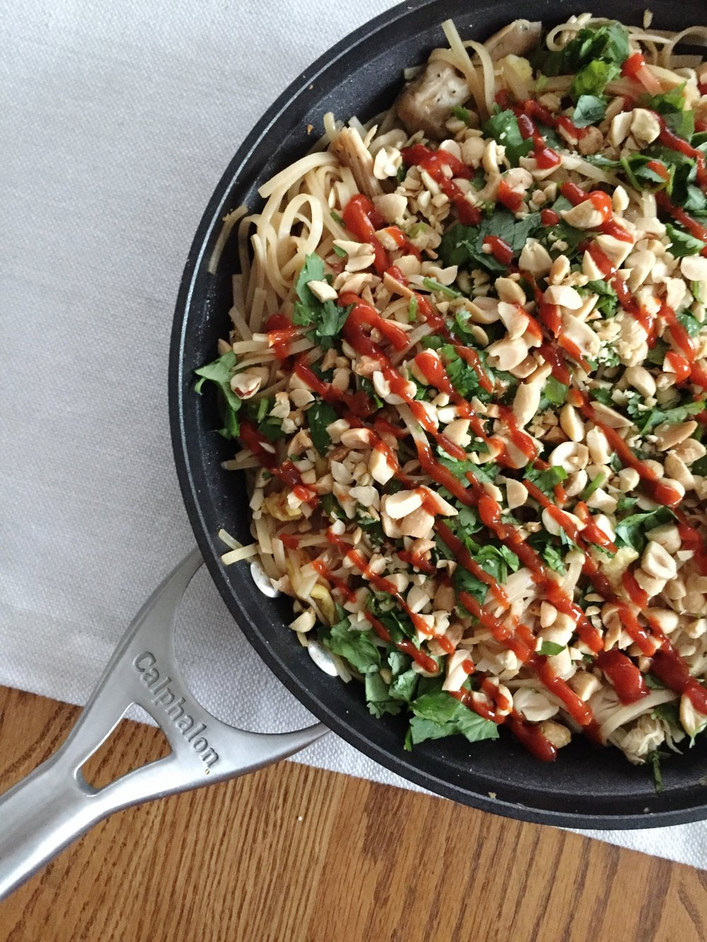 skillet of pad thai with sriracha sauce