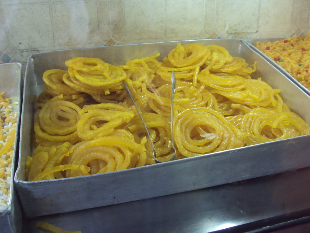 """The Middle Eastern treat known as  jalebi . To quote Skiz from Rice and Curry (photo credit): """"These spiral rings filled with honey are made from a fermented wheat flour that is deep fried in ghee (of course) and then soaked in a heavy syrup until they become tentacles that squirt pure sweetness in every bite"""". Yum :)"""