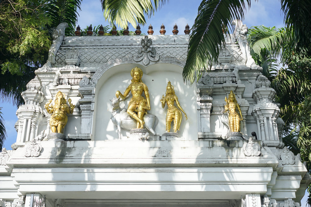 Lord Shiva (on his vehicle of the holy cow), his wife Parvati and their sons Ganeshan and Murugan above the entrance to the Sri Ponnambalam Vanesar Kovil on the port side