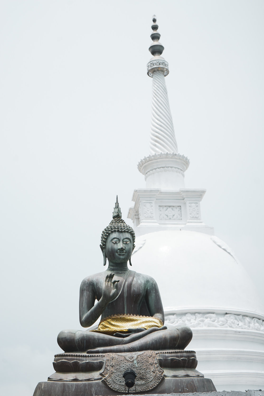 Stupa and bronze Buddha in yoga pose