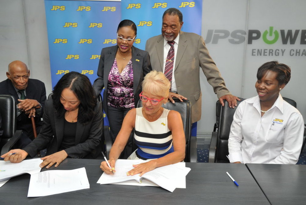 Mayor of Savanna-la-Mar, Councillor Bertel Moore and JPS Legal Counsel Teri-Ann Gibbs (standing), closely observe as JPS President & CEO, Kelly Tomblin (2nd right) signs a Power Purchase Agreement with Angella Rainford of Eight Rivers Energy. Under the agreement, JPS will purchase power from the solar provider, for 20 years, up to the year 2038. The solar plant, which will be constructed in Paradise, Westmoreland will generate 37MW of electricity. Looking on are Attorney at Law, Frank Phipps (far left) and JPS Manager for Special Projects, Dionne Nugent.