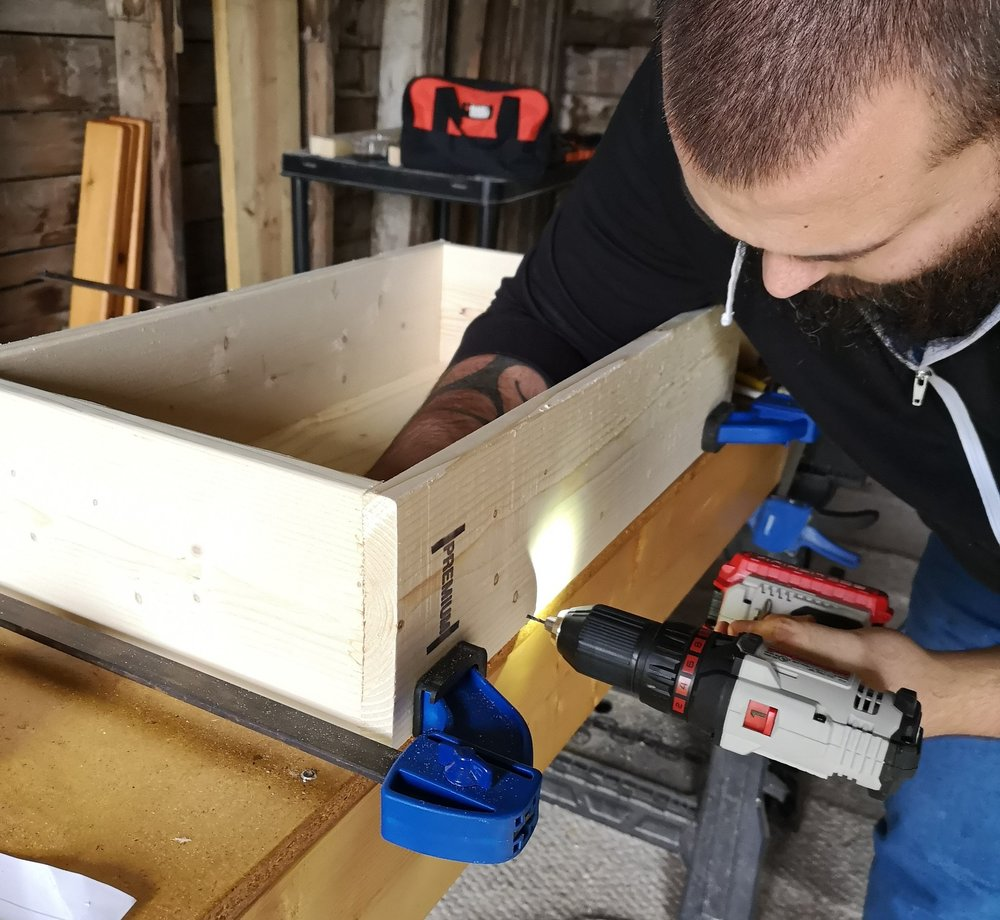 Drilling the pilot holes in the back of the drawer to ensure the bottom stays in place.