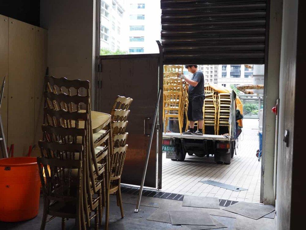 跟在燈光音響後面,現場的桌椅也開始進場了,這次選用的是搭配白綠青主題、金色的竹節椅和銀灰色的桌布。