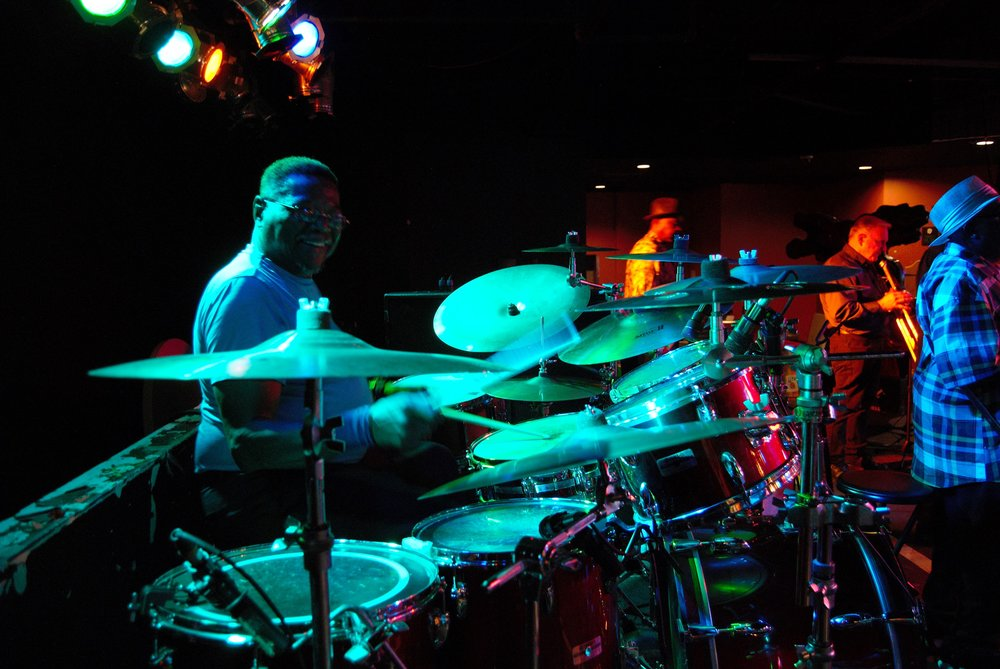 Steve Gilmore - Drummer, Steve Gilmore (older brother of André), began playing drums at age four. His semi-professional music career started while in high school, sitting in nightclubs with some of Chicago's finest musicians and as a percussion major at St. Mary's College (now University) in Winona, MN. His biggest highlight as part of the Mt. Mary's jazz band was arranging and performing in concert with legendary trumpeter Clark Terry . Steve played in the following bands: Innervision, Phaerus, Brown-Hill Ensemble, and helped found the Jazz/Fusion group Extension, who recorded a CD of original music in 1994.Steve holds a Bachelor of Music degree in percussion performance, and is equally at home behind a trap set, congas, or auxiliary percussion.