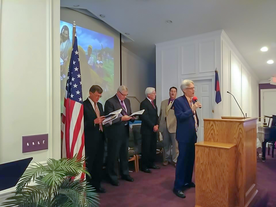 """Mike Duman, pastor, leads a congregational song while Dennis Milburn (left), former treasurer of Gulf States, Dave Livermore, president of the Gulf States conference, Mel Eisele, former president of Gulf States, and Michael Abraham, local elder, sing along for the ceremony."""""""