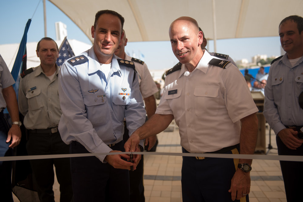 Israel and U.S. and Israeli Commanders cutting the ribbon to open a new U.S. military base in Israel on Sept. 18.  Brig. Gen. Zvika Haimovich, commander of the Israel Air Force's Aerial Defense Division is on the left. He is wearing a light blue full-sleeved shirt with three stars on each shoulder. Maj. Gen. John Gronski, deputy commander of the U.S. Army National Guard in Europe, is on the right. He is wearing a white, short-sleeved shirt.