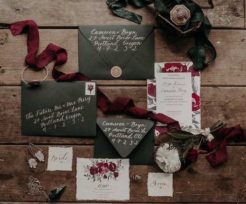 The Bryn  The Bryn features moody burgundy and red florals, customized calligraphed names and envelope color of your choosing. The Bryn style starts at $225 for 100 invitation sets including the invitation, rsvp and blank envelopes for the invitation and rsvp.