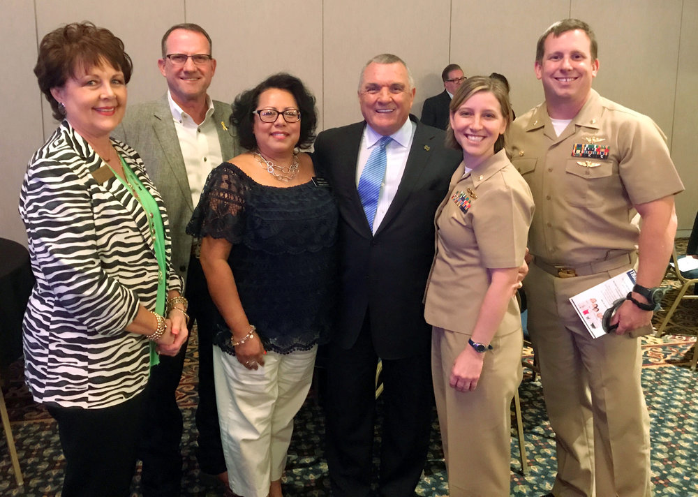 """Representatives from America - Celebrate, Honor & Serve pose with famed Notre Dame football player Daniel """"Rudy"""" Ruettiger"""