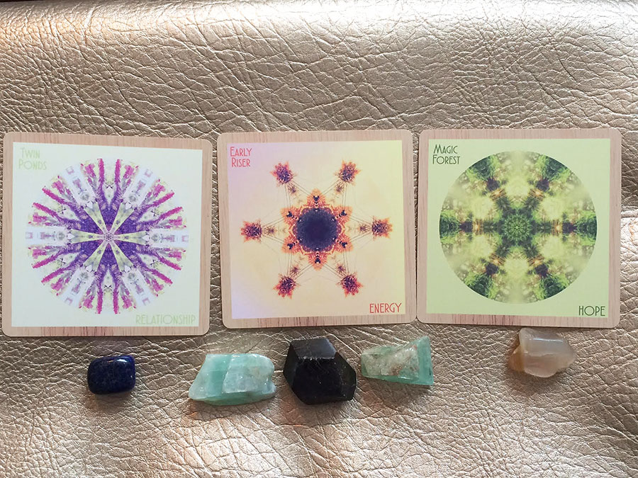 Cards: Twin Ponds/RELATIONSHIP, Early Riser/ENERGY, Magic Forest/HOPE. Crystals: lapis lazuli for self-acceptance, green calcite and garnet for an open heart, peach moonstone for inner wisdom, joy and magic.