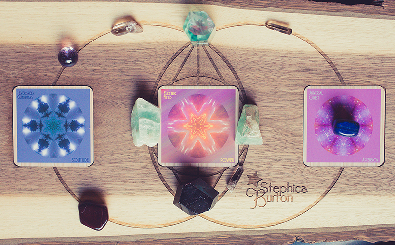 Cards: Evergreen Guardians/SOLITUDE, Electric Field/POWER, Universal Quest/ASCENSION Crystals: green calcite, garnet and red tiger's eye for compassionate personal power, green/purple fluorite wand for smooth transitions, amethyst and smokey quartz for boundaries, lapis lazuli for self-knowledge.