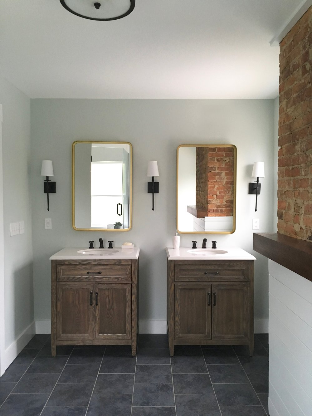 After: dual vanities create balance and symmetry. The glass door to the walk-in shower is visible in the left mirror.
