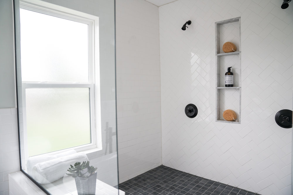 After: a spacious walk-in shower with a tiled bench.
