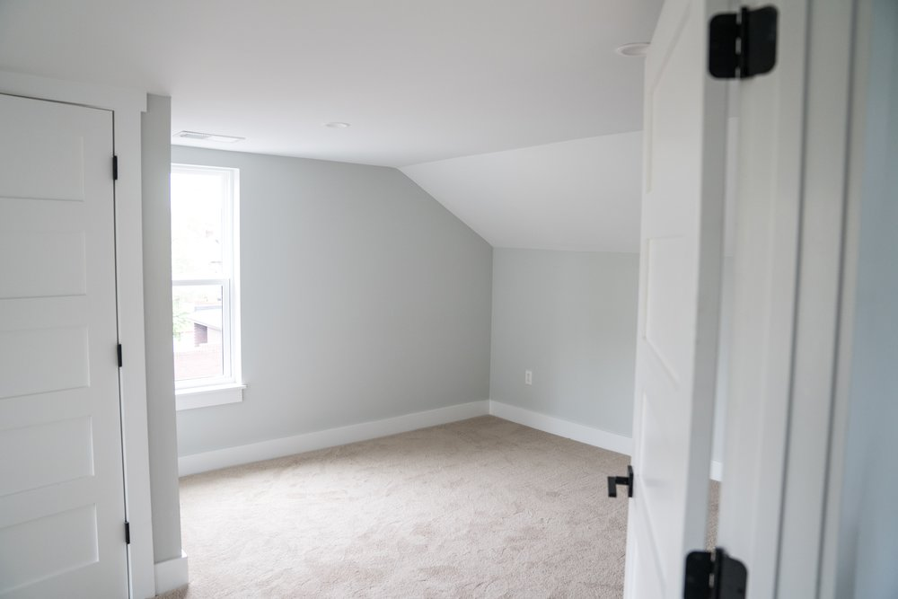 After: two cramped bedrooms were combined into a single larger bedroom by removing the dividing wall and brick fireplace stack. A walk-in closet was tucked under the sloped ceiling line on the left.