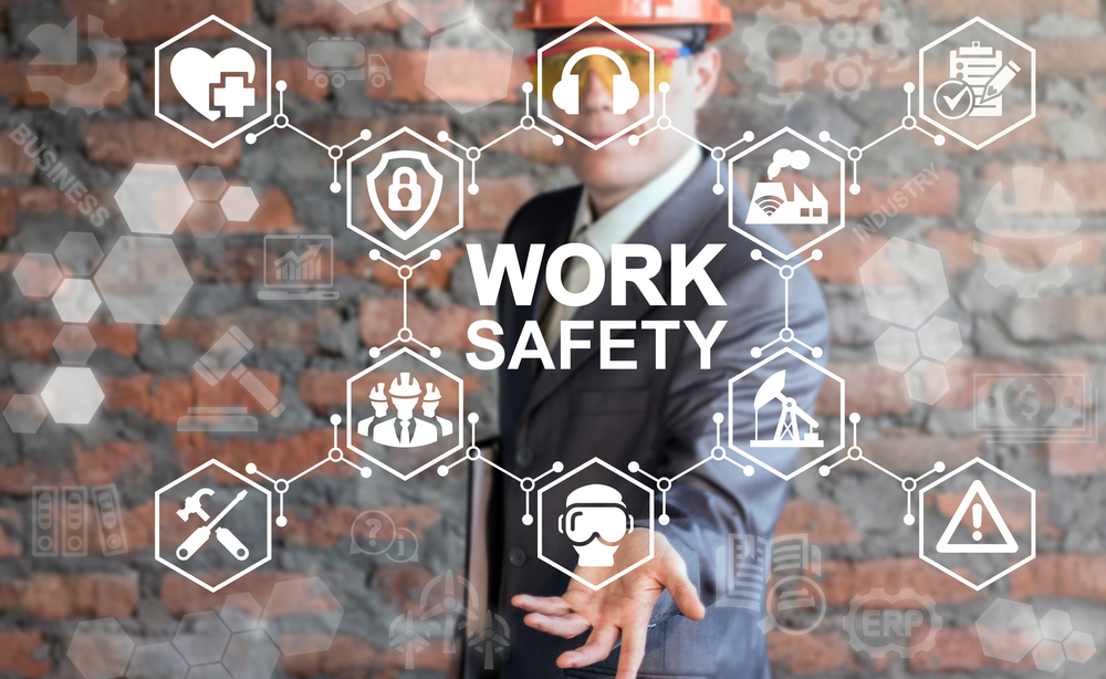 Man with hard hat holding hand under virtual images of work safety