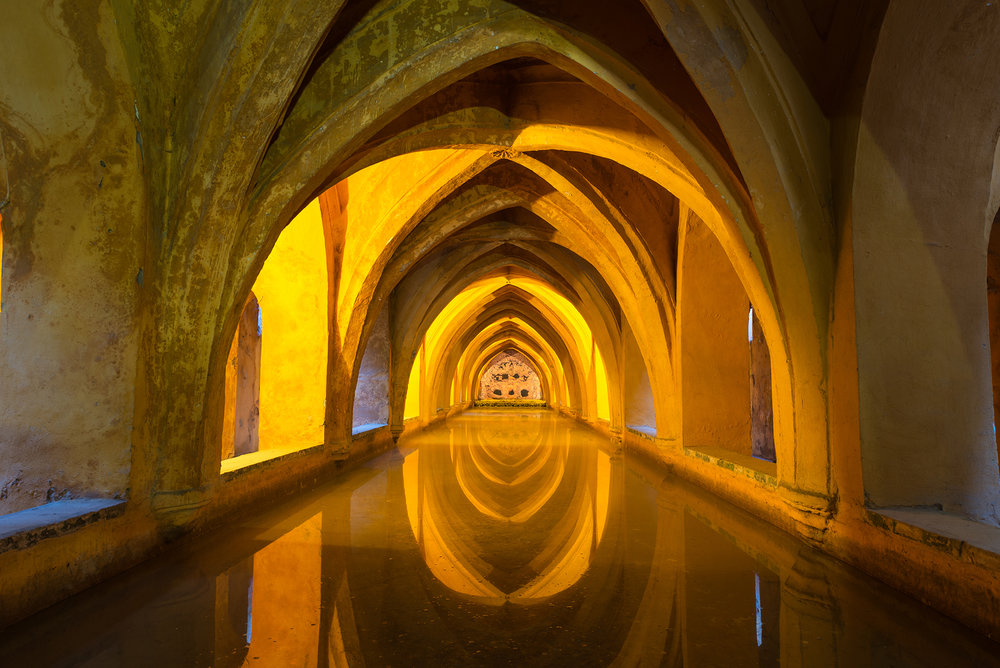 Illuminated ancient baths below the Alcázar