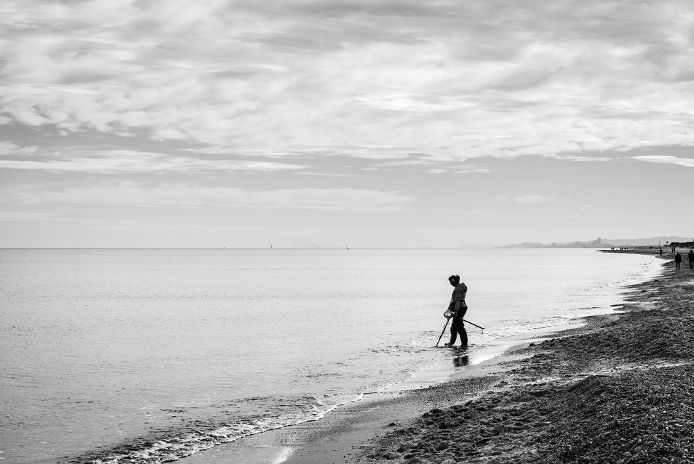 Silhouette of a female treasure hunter with a metal detector on a beach in the Mediterranean sea