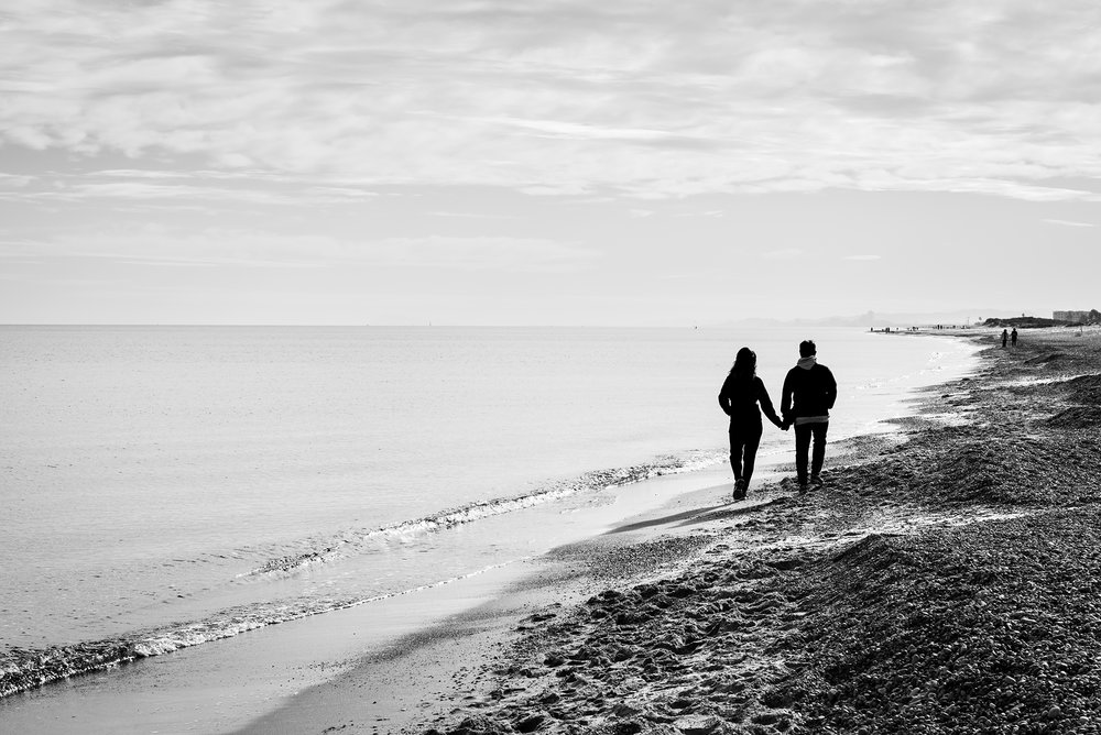 Silhouette of a couple holding hands while walking along the shore of the Mediterranean sea