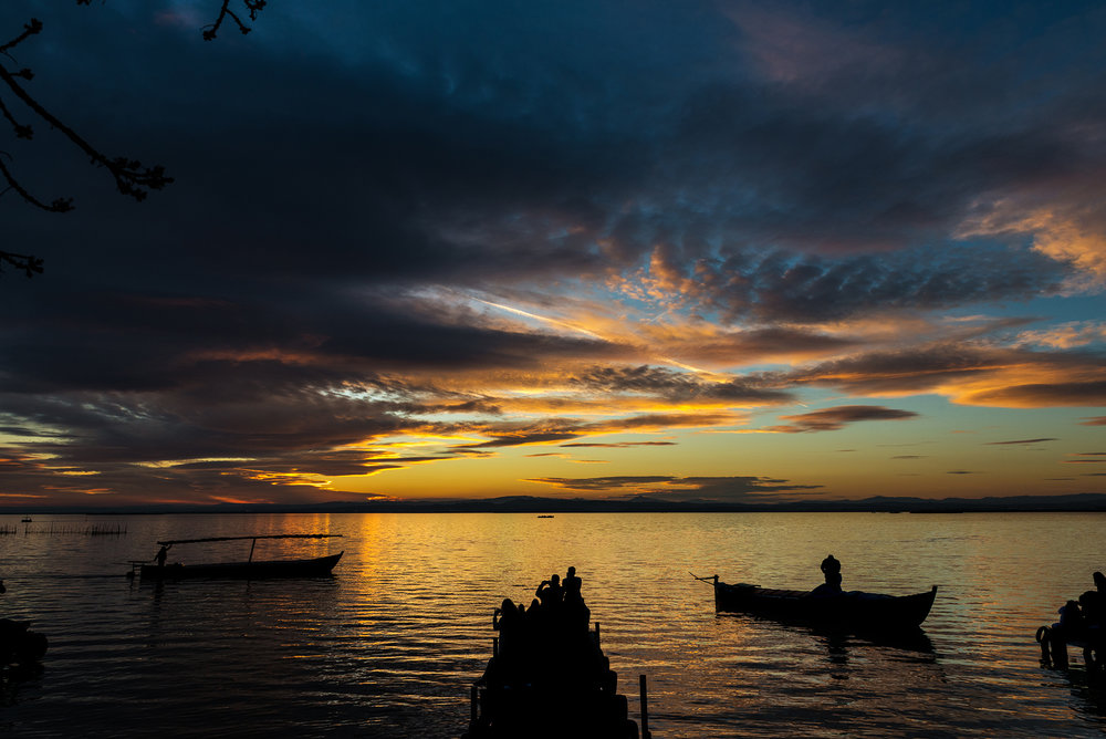Silhouette of small traditional boats and tourists at dusk in the Albufera