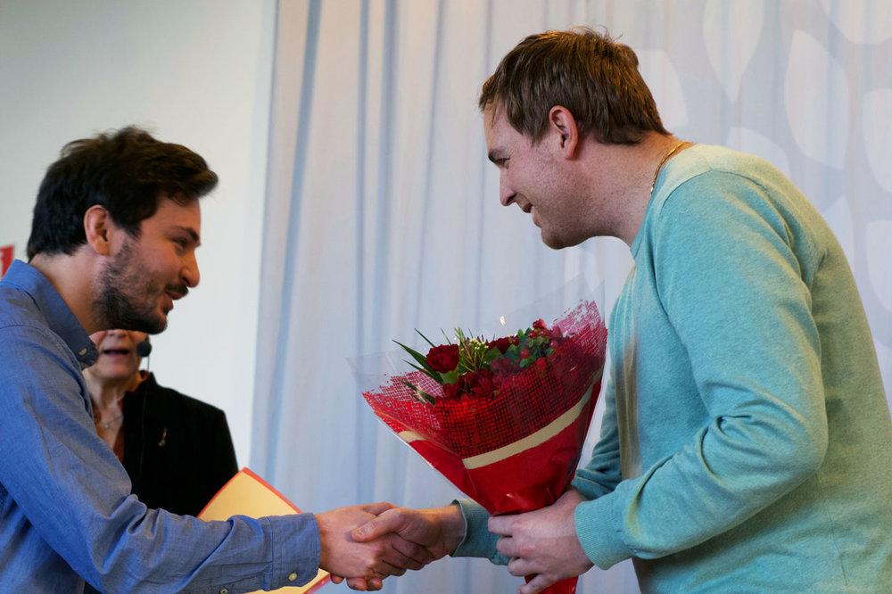 Rickard Albo tar emot blommor från Samuel Fried