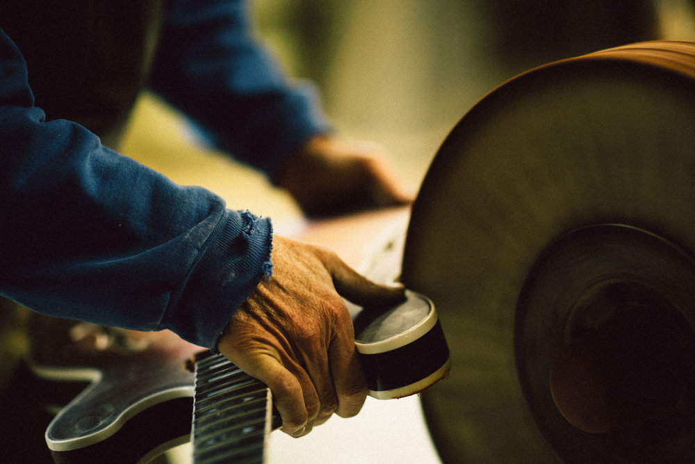 A worker buffing a semi-hollow double cutaway.