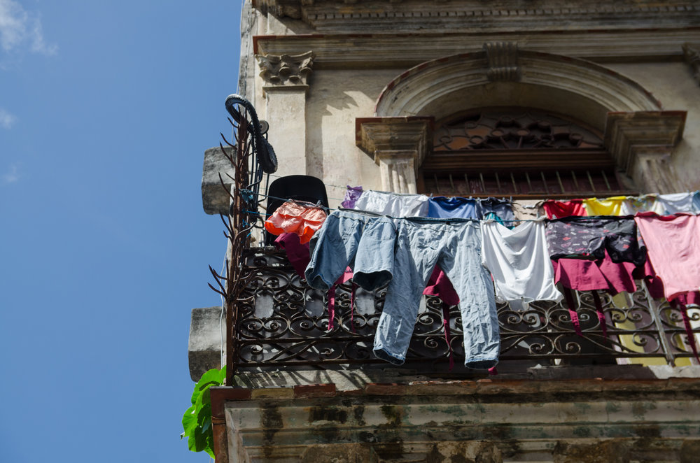 Color clothing hanging on a clothesline. The clothesline is strung across a balcony in Havana, Cuba, and there is a blue sky in the background.